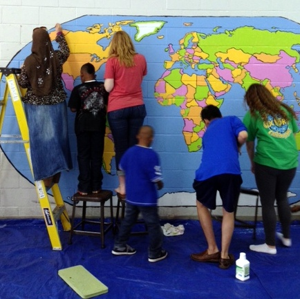 Rebel Global Connections members paining a mural of the world in Clarksdale.